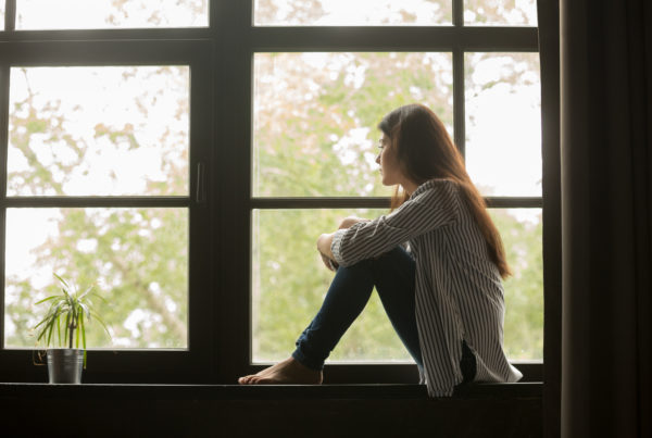 Depressed woman sitting on window sill
